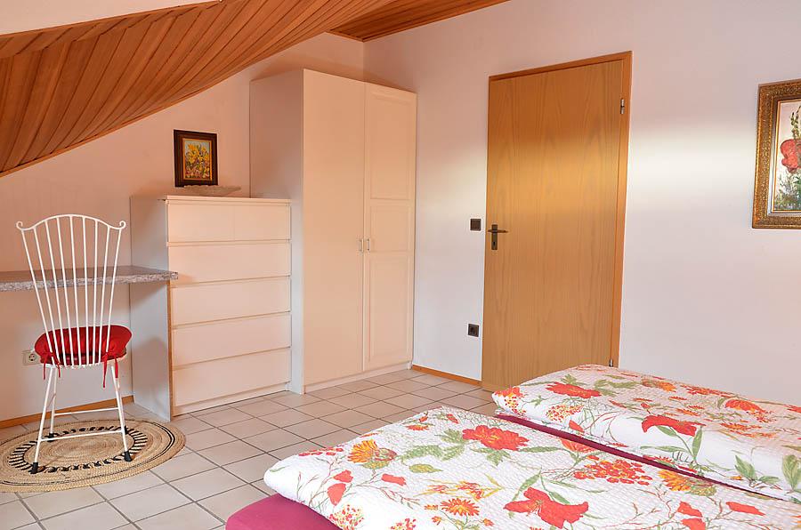 Individuell eingerichtetes Schlafzimmer mit Doppelbett, Schrank und Kommode.