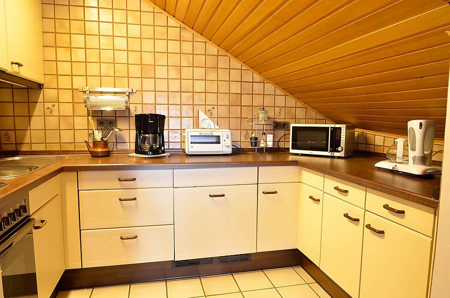 Voll ausgestattete Einbauküche mit offenem Zugang zum Wohnraum.