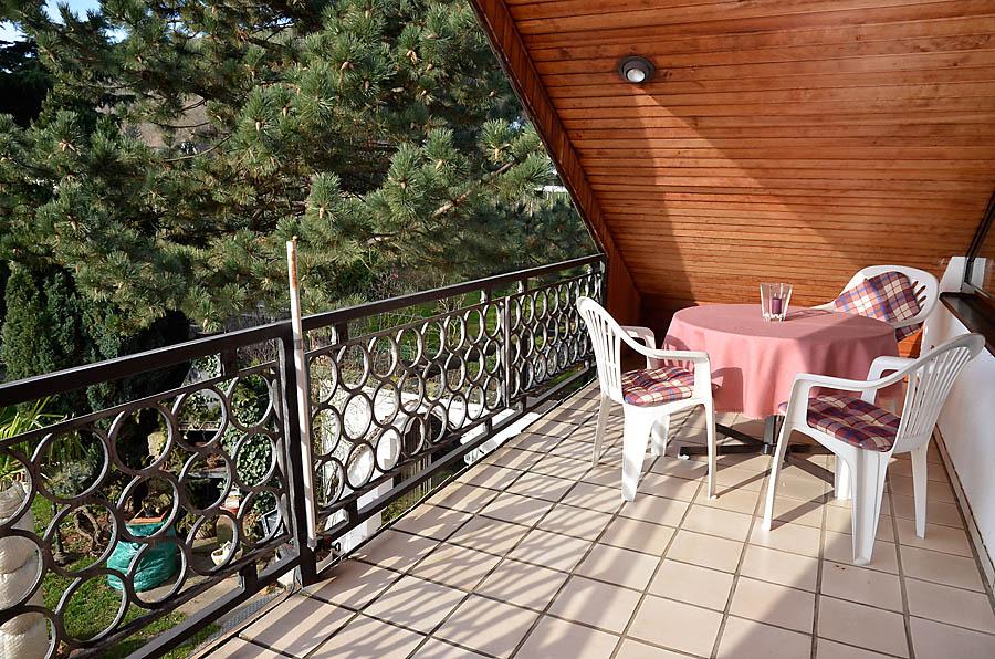 Übedachter Balkon mit Panoramablick in den Garten, auf die Rebflächen und den Pfälzerwald.